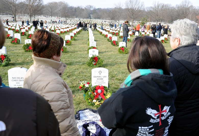 Susan Zerbe, left, and Megan Zerbe, middle, look down at Tech. Sgt. Daniel Zerbe's grave after laying a wreath on it during the 23rd Annual National Wreaths Across America Day Dec. 13, 2014, at Arlington National Cemetery, Virginia. Susan is Daniel's mother and Megan is his sister. Airmen from all around the Washington D.C. area, along with friends and families of fallen warriors were among the nearly 50,000 volunteers to place remembrance wreaths on the headstones of about 230,000 veterans. (U.S. Air Force photo/Staff Sgt. Christopher Gross)