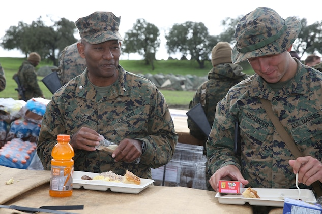 U.S. Navy Commander Samuel Ravelo, left, eats lunch with U.S. Marines from Headquarters and Service Company, Battalion Landing Team 3rd Battalion, 1st Marine Regiment, during realistic urban training aboard Camp Roberts, Calif., Dec. 12, 2014. Ravelo is the chaplain of the 15th Marine Expeditionary Unit. The purpose of RUT is to provide the MEU the opportunity to conduct training in unfamiliar environments in preparation for their upcoming deployment. (U.S. Marine Corps photo by Cpl. Anna Albrecht/ Released)