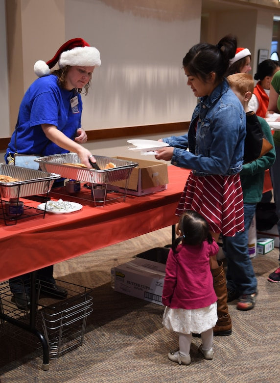 A volunteer serves breakfast to Team Buckley members at the annual Breakfast with Santa event Dec. 14, 2014, at the Leadership Development Center on base. At the event, Team Buckley had the opportunity to meet Mr. and Mrs. Claus, grab a pancake breakfast and pick out their favorites from a variety of gifts to raise holiday spirit. (U.S. Air Force photo by Airman 1st Class Emily E. Amyotte/Released)