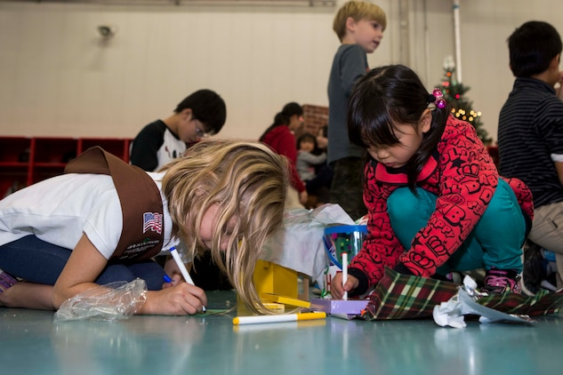 Leia Rasmussen, 7, left, a brownie with the Marine Corps Air Station Iwakuni Girl Scouts, makes a note for a member of the Tsuta Children's Home during the Aircraft Rescue Firefighting holiday party, Dec. 12, 2014, inside the ARFF compound aboard MCAS Iwakuni, Japan. The holiday party was hosted as part of an existing relationship between ARFF and the Tsuta Children's Home; where members of ARFF invite the children's home aboard station to spread holiday cheer.