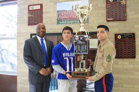 (From left to right) Dr. Jeffery Woodberry, principal of Half Hollow Hills East High School, Rob Mora, a participant in last year's Inaugural Dan Daly Cup, and Staff Sgt. Henry Zapata, recruiter with Recruiting Substation Lindenhurst, pose for a photo with the Dan Daly Cup trophy. The cup will be showcased in each of the schools of the players from the winning team, Team Valor. It will be located at Half Hollow Hill East High School until Jan. 5.