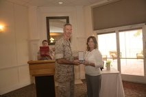 Col. Timothy Salmon, the commanding officer of Marine Corps Air Station New River, stands with Kathy Zerba, his former office management specialist and community liaison coordinator, after she was recognized with the meritorious civilian service award during a surprise farewell celebration in her honor, at the Eagles Nest Officers' Club aboard Marine Corps Air Station New River, July 10. Zerba is joining the staff of Naval Hospital Camp Lejeune after nine years of service at MCAS New River.