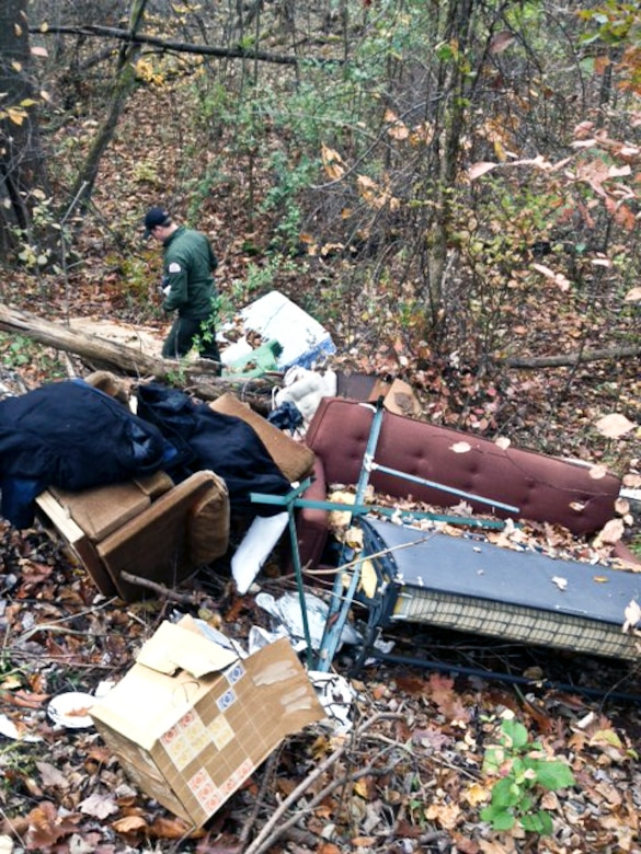 Ranger Kyle Kraynak searches through dumped debris and household goods for owner's identification or information.
