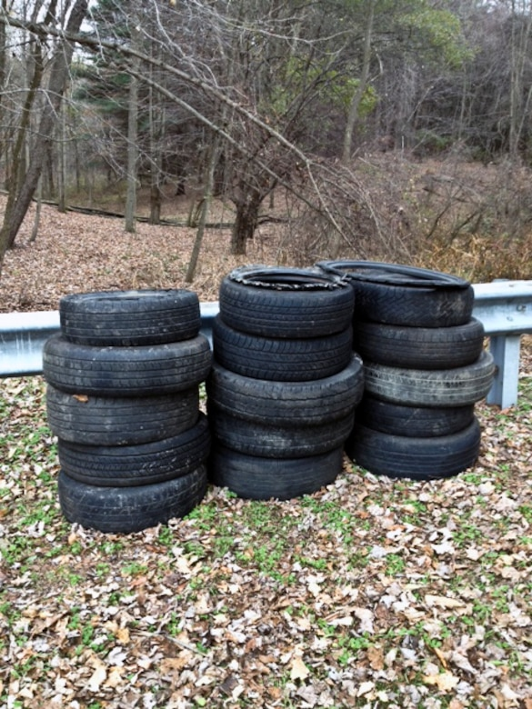 A stack of discarded tires found in a lake access parking lot.