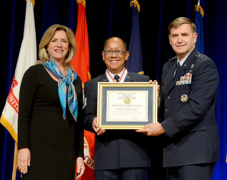 Secretary of the Air Force Deborah Lee James and Air Force Assistant Vice Chief of Staff Lt. Gen. Stephen Hoog present retired Tech. Sgt. Victor Pulido III the Spirit of Hope Award during a ceremony in the Pentagon, Dec. 11, 2014.  The award is presented to individuals or organizations from each of the military services whose patriotism and service to members of the U.S. Armed Forces reflects the patriotism and service of Bob Hope.  (U.S. Air Force photo/Scott M. Ash)