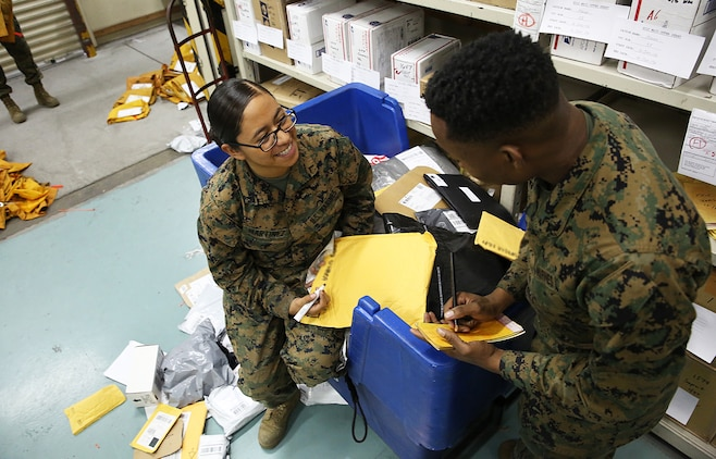Pfc. Maria Martinez, directorary clerk at the Mainside Postal Office aboard Marine Corps Air Station Iwakuni, Japan, goes through mail on Dec. 11, 2014. More than 700 pounds of mail are sent per day and 3,500 pounds of mail are received per day during the busy holiday season months of late November to mid-January.