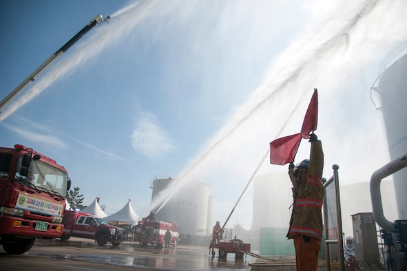 Kunsan Air Base firefighters, alongside Gunsan City firefighters, extinguish a simulated fire during an emergency-relief exercise in Gunsan City, Republic of Korea, Nov. 5, 2014. The purpose of the exercise was to establish an incident command system between multiple organizations and enhance their ability to respond to emergencies and large disasters. (U.S. Air Force photo by Senior Airman Taylor Curry/Released)