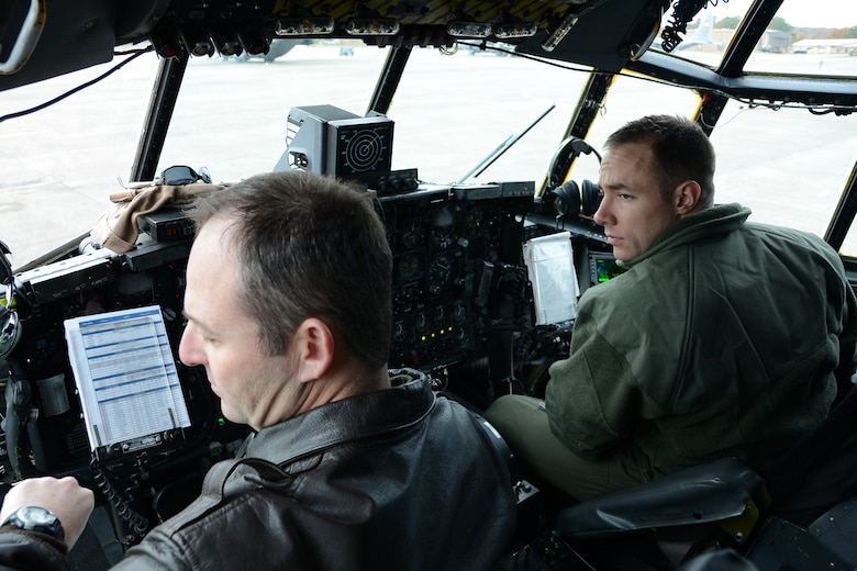 """Lt. Col. William Daniels and Capt. Paul Bolduc, both pilots with the 103rd Operations Group prepare for takeoff at the controls of a C-130H Hercules aircraft assigned to the 103rd Airlift Wing, shortly after maintainers from the 103rd Maintenance Group prepared the aircraft as part of the unit's first C-130H engine generation exercise, Nov. 1, 2014 at Bradley Air National Guard Base, East Granby, Conn.  """"An aircraft generation is basically a sequence of events we follow to configure the aircraft for a particular mission within a specified timeframe,"""" said Master Sgt. Jonas Concepcion, production superintendent for the 103rd Maintenance Group.  (U.S. Air National Guard photo illustration by Maj. Bryon M. Turner)"""