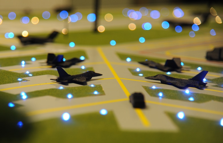 3-D printed aircraft models sit on top of an illuminated airfield training aid table used in the 334th Training Squadron airfield management course Dec. 12, 2014, at Cody Hall, Keesler Air Force Base, Miss.  Utilizing the model, which is a scaled representation of an airfield, will increases understanding, productivity and efficiency in the classroom. (U.S. Air Force photo by Kemberly Groue)