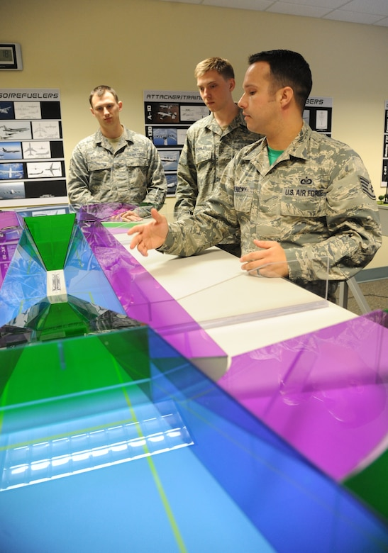 Senior Airmen Ryan Rathke and Marc Stanley, 334th Training Squadron students, listen to Staff Sgt. Courtney Polnicky, 334th TRS airfield management instructor, discuss the training capabilities the new model airfield training aid table offers Dec. 12, 2014, at Cody Hall, Keesler Air Force Base, Miss.  Utilizing the model, which is a scaled representation of an airfield, will increases understanding, productivity and efficiency in the classroom. (U.S. Air Force photo by Kemberly Groue)