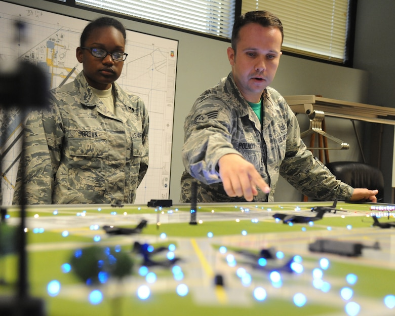 Airman Basic Marquise Jordan, 334th Training Squadron student, watches as Staff Sgt. Courtney Polnicky, 334th TRS airfield management instructor, points out the 3-D printed aircraft models on the new model airfield training aid table Dec. 12, 2014, at Cody Hall, Keesler Air Force Base, Miss.  Utilizing the model, which is a scaled representation of an airfield, will increases understanding, productivity and efficiency in the classroom.  (U.S. Air Force photo by Kemberly Groue)