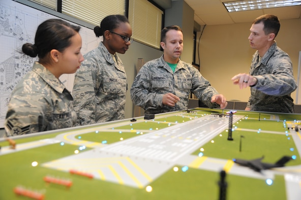Airman 1st Class Kathryn Infantino and Airman Basic Marquise Jordan, 334th Training Squadron students, stand by while Staff Sgt. Courtney Polnicky, 334th TRS airfield management instructor, and Senior Airman Ryan Rathke, 334th TRS student, discuss the training capabilities the new model airfield training aid table offers Dec. 12, 2014, at Cody Hall, Keesler Air Force Base, Miss.  Utilizing the model, which is a scaled representation of an airfield, will increase understanding, productivity and efficiency in the classroom.  (U.S. Air Force photo by Kemberly Groue)