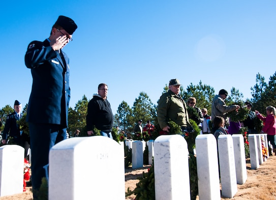 A volunteer salutes a gravestone after laying his wreath at the Wreaths Across America ceremony in Canton, Ga. at Georgia National Cemetery Dec. 13, 2014. Thousands showed up to GNC to honor America's heroes. (U.S. Air Force photo/Senior Airman Daniel Phelps))