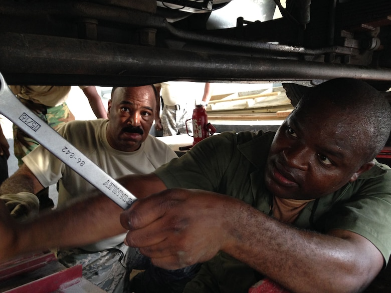 Senior Airman Renardo Butler (left) observes as Jamaican Defence Force civilian mechanic Lance Corporal Newland J. works on aligning a wheel on a 2.5-ton Jamaican Defence Force freightload truck. Butler, a vehicle mechanic from the 113th Wing, D.C. Air National Guard at Joint Base Andrews, Md., and Kemp are participating in a subject matter expert exchange under the National Guard Bureau's State Partnership Program. (U.S. Air National Guard photo by Capt. Renee Lee)