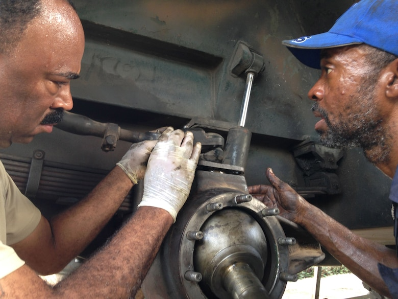Jamaican Defence Force civilian vehicle mechanic Mr. Dean Kemp and Senior Airman Renardo Butler secures a wheel stud and lock into place on a 2.5-ton Jamaican Defence Force freightload truck. Butler, a vehicle mechanic from the 113th Wing, D.C. Air National Guard at Joint Base Andrews, Md., and Kemp are participating in a subject matter expert exchange under the National Guard Bureau's State Partnership Program. (U.S. Air National Guard photo by Capt. Renee Lee)