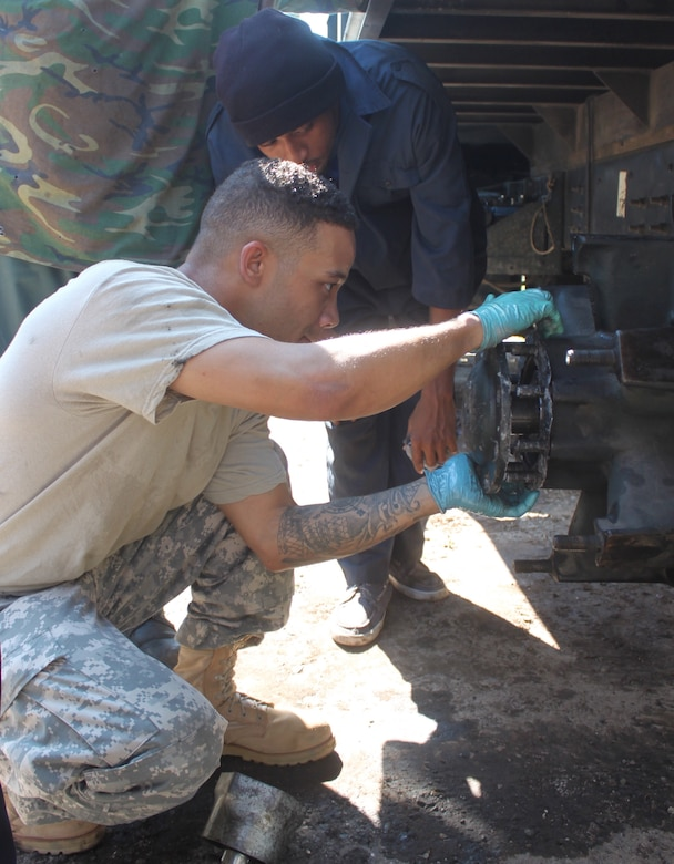 Sgt. Girard King secures a wheel stud and lock into place on a 2.5-ton Jamaican Defence Force freightload truck with the assistance of Jamaican Defence Force civilian mechanic Mr. Allan S. King, a vehicle mechanic with the 273rd Military Police Co., D.C. National Guard, at Joint Base Anacostia-Bolling in Washington, is participating in a subject matter expert exchange with the JDF under the National Guard Bureau's State Partnership Program. (U.S. Air National Guard photo by Capt. Renee Lee)