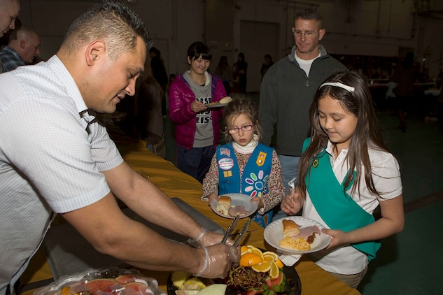 Gunnery Sgt. Nathan Lanham, the embarkation chief with Aircraft Rescue Firefighting, passes out fruit to guest of ARFF's annual holiday party, Dec. 12, 2014, inside the ARFF compound aboard Marine Corps Air Station Iwakuni, Japan. The holiday party was hosted as part of an existing relationship between ARFF and the Tsuta Children's Home, where members of ARFF invite the children's home aboard station to spread holiday cheer.