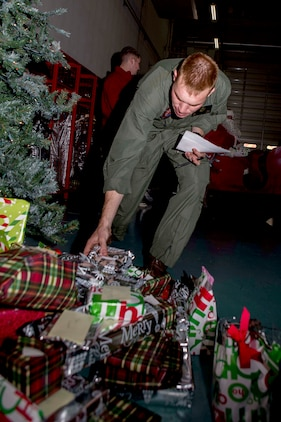 Cpl. Phillip King, an Aircraft Rescue Firefighter with Headquarters and Headquarters Squadron, grabs presents for station youth and members of the Tsuta Children's Home during ARFF's holiday party, Dec. 12, 2014, inside the ARFF compound, aboard Marine Corps Air Station Iwakuni, Japan. The holiday party was hosted as part of an existing relationship between ARFF and the Tsuta Children's Home, where members of ARFF invite the children's home aboard station to spread holiday cheer.