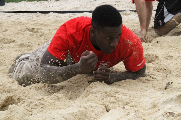 Kalen Banks, a candidate from Marine Corps Officer Selection Team Cincinnati, low crawls through a volleyball sand pit during a pool function at the University of Dayton, Oct. 25, 2014. The pool function consisted of a 45-minute physical training session where the group of approximately 40 Marines and applicants completed a run around campus and land navigation training. (U.S. Marine Corps photo by Sgt. Jennifer Pirante)