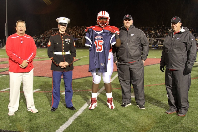 George Asafo-Adjei, 18, of West Chester, Ohio, an offensive lineman for Lakota West High School, was recognized for being selected to play football during the Marine Corps Semper Fidelis All-American Bowl Oct. 31.  Sgt. Ethan Millisor, recruiter from Marine Recruiting Substation Fairfield, Ohio, and alumni football player, presented Asafo-Adjei with a SFAAB hat, shirt and football jersey at the start of one of the biggest rivalry football games in town, Lakota West vs. Lakota East High School. (U.S. Marine Corps photo by Sgt. Jennifer Pirante/Released)