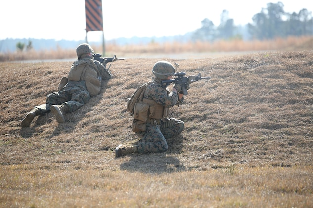Marines with Company A, Ground Combat Element Integrated Task Force, execute an assault on a simulated enemy position during a fire team collective skills exercise at Range K509, Marine Corps Base Camp Lejeune, North Carolina, Dec. 16, 2014. The Marines utilized the M4 carbine rifle and M16-A4 service rifle, as well as the M27 Infantry Automatic Rifle and M203 grenade launcher. From October 2014 to July 2015, the Ground Combat Element Integrated Task Force will conduct individual and collective skills training in designated combat arms occupational specialties in order to facilitate the standards based assessment of the physical performance of Marines in a simulated operating environment performing specific ground combat arms tasks. (U.S. Marine Corps photo by Cpl. Paul S. Martinez/Released)