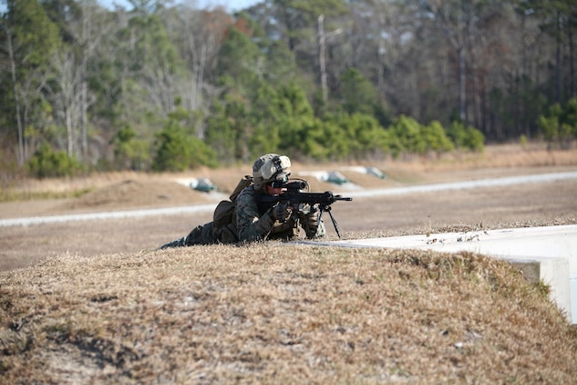 Lance Cpl. Max D. Tackett, rifleman, Company A, Ground Combat Element Integrated Task Force, executes an assault on a simulated enemy position during a fire team collective skills exercise at Range K509, Marine Corps Base Camp Lejeune, North Carolina, Dec. 16, 2014. The Marines utilized the M4 carbine rifle and M16-A4 service rifle, as well as the M27 Infantry Automatic Rifle and M203 grenade launcher. From October 2014 to July 2015, the Ground Combat Element Integrated Task Force will conduct individual and collective skills training in designated combat arms occupational specialties in order to facilitate the standards based assessment of the physical performance of Marines in a simulated operating environment performing specific ground combat arms tasks. (U.S. Marine Corps photo by Cpl. Paul S. Martinez/Released)