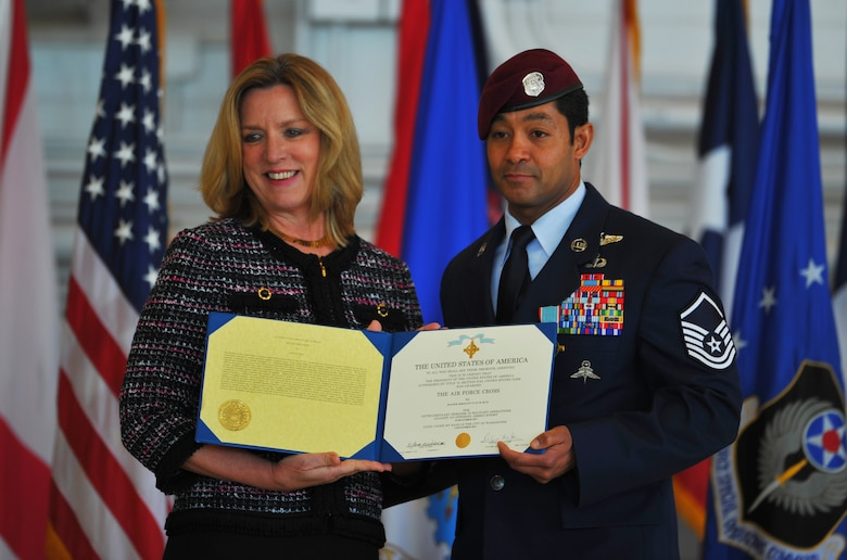Master Sgt. Ivan Ruiz, a pararescueman from the 56th Rescue Squadron, Royal Air Force Lakenheath, England, displays his Air Force Cross citation with Secretary of the Air Force Deborah Lee James at the Freedom Hangar on Hurlburt Field, Fla., Dec 17, 2014. Ruiz earned the Air Force Cross while deployed with the 22nd Expeditionary Special Tactics Squadron, and assigned to the 23rd STS at Hurlburt Field, Fla. The last six Air Force Crosses have all been awarded to AFSOC Special Tactics Airmen.  (U.S. Air Force photo/Airman 1st Class Jeff Parkinson)