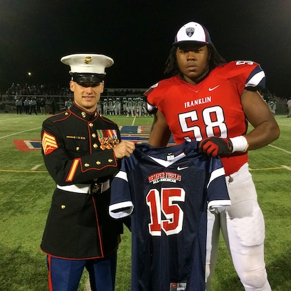 U.S. Marine Sgt. Evan A. Page, a recruiter with Marine Corps Recruiting Station Baltimore, and a native of Baltimore, presents a jersey to Patrick Allen at Franklin High School in Reisterstown, Maryland, October 24. Allen, an offensive tackle for Franklin High's football team, has been selected to play in the 2015 Semper Fidelis All-American Bowl, which will be played in Carson, California in January. (U.S. Marine Corps photo by Sgt. Bryan Nygaard/Released)