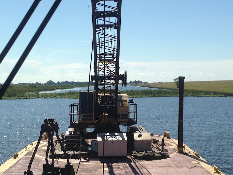 The tug boat Leitner pushed a barge mounted crane into position so a crew could break up and remove a half-acre tussock or floating island, restoring navigation along the Rim Canal Route 2 of the Okeechobee Waterway and the south side of Lake Okeechobee.