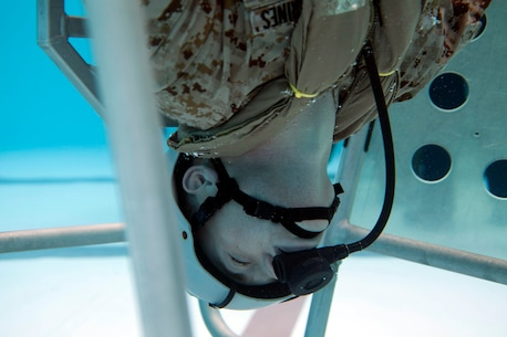 A Marine sits upside down in a shallow water egress trainer chair during Underwater Egress Training Dec. 9 at the Hansen Aquatics Center. The Marines conducting the training are with Combat Logistics Battalion 31, 31st Marine Expeditionary Unit, and they are conducting pre-deployment preparations for the regularly-scheduled Spring Patrol of the Asia-Pacific region. (U.S. Marine Corps photo by Lance Cpl. Richard Currier/Released)