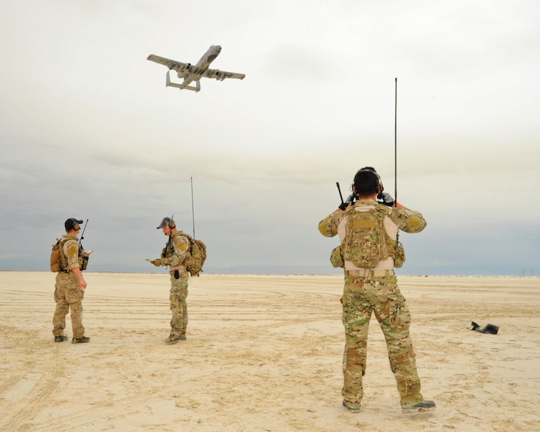U.S. Air Force combat controllers from the 23rd Special Tactics Squadron, Hurlburt Field, Fla., perform air traffic control radio transmissions to an A-10C Thunderbolt II pilot of the 354th Fighter Squadron, Davis-Monthan Air Force Base, Ariz., approaching an austere landing strip during training at White Sands Missile Range, N.M., Dec. 4, 2014.  The combat controllers set up the landing strip as part of their initial and reoccurring training.  (U.S. Air Force photo by Airman 1st Class Chris Massey/Released)