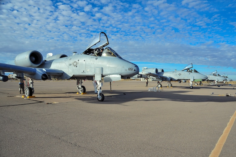 Four A-10C Thunderbolt IIs from the 354th Fighter Squadron, Davis-Monthan Air Force Base, Ariz., sit on the flightline at Holloman Air Force Base, N.M., after a training flight at White Sands Missile Range, N.M., Dec. 3, 2014.  The austere conditions of the missile range allow for pilots to get a close simulation of a deployed environment.  (U.S. Air Force photo by Airman 1st Class Chris Massey/Released)
