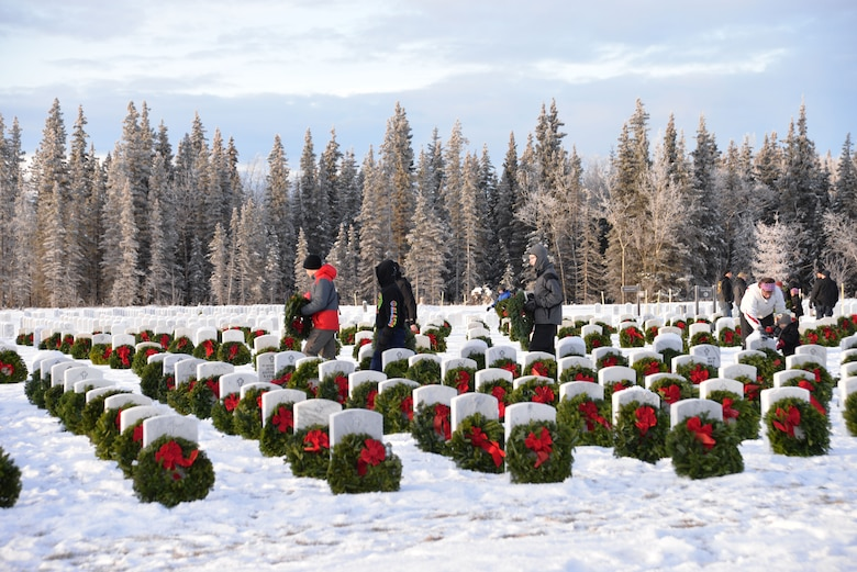 "Volunteers place wreaths on gravestones at Fort Richardson National Cemetery Dec. 13 during the local observance of ""Wreaths Across America,"" a nationwide program honoring fallen veterans each holiday season. (U.S. Air Force photo/Song Johnson)"
