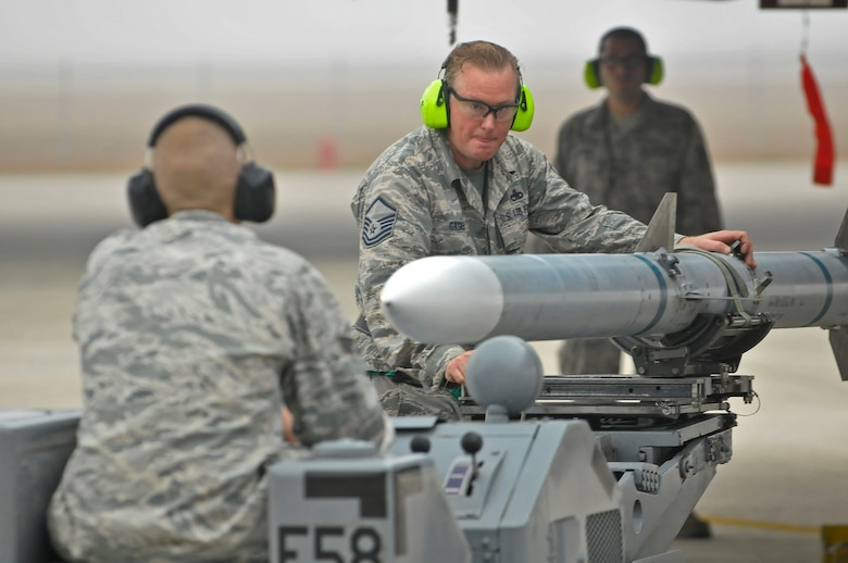 U.S. Air Force Airman Master Sgt. David Gaskins works as a weapons load crew member during a  load crew challenge for Valiant Eagle 2014 at the 125th Fighter Wing, Jacksonville, Fla. on December 5, 2014 (U.S. Air National Guard photo by Staff Sgt. Troy Anderson // Released)