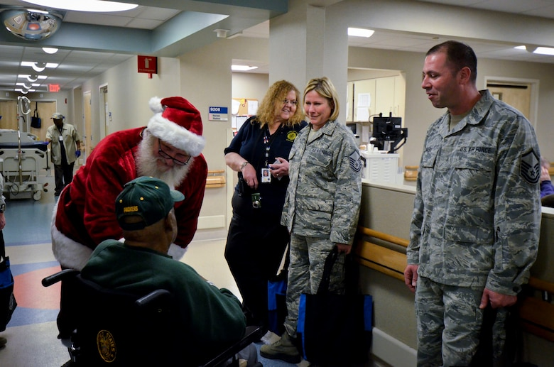 Santa and U.S. Airmen with the 128th Air Refueling Wing visit with a patient while passing out gifts to veterans at the Clement J. Zablocki VA Medical Center, Milwaukee Dec. 10, 2014.  (U.S. Air National Guard photo by Tech. Sgt. Jenna Lenski/Released)