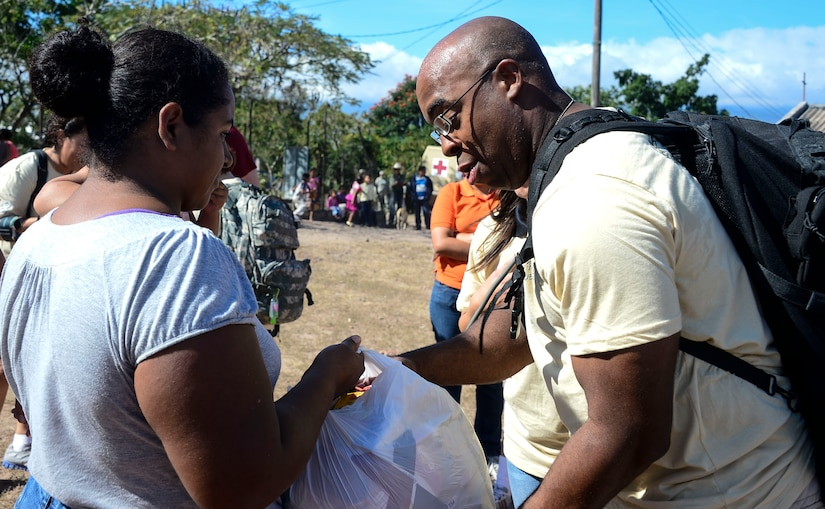 U.S. Army Master Sgt. Leon Fletcher, Medical Element first sergeant, gives one of the villagers a bag of donated food during the 58th Chapel Hike in the village of Mira Valle, La Paz, Honduras, Dec. 13, 2014. As part of the 58th Chapel Hike, over 130167 members assigned to Joint Task Force-Bravo trekked over three miles to help deliver over 3,5002,500-pounds of donated dry goods to villagers in need. Since the chapel hikes originated in 2007, over 9,700 service members have donated over $170,000 and volunteered their time to deliver more than 209,000 pounds of food and supplies to several remote villages. (U.S. Air Force photo/Tech. Sgt. Heather Redman)