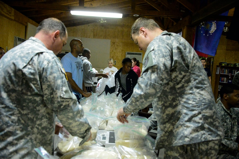 Volunteers gather at the Chapel's activity room to help fill 130 bags of food on Soto Cano Air Base, Honduras, Dec. 11, 2014.  The food will be donated to families in the village of Mira Valle, La Paz, Honduras when volunteers from Soto Cano AB head off on the 58th Chapel Hike.  Since the chapel hikes originated in 2007, over 9,700 service members have donated over $170,000 and volunteered their time to deliver more than 209,000 pounds of food and supplies to several remote villages.