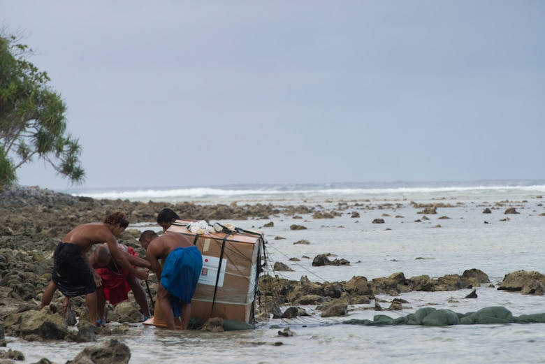 Islanders rush to lift a package out of the water during Operation Christmas Drop Dec. 9, 2014, at Ulithi Atoll, Micronesia. The bundle weighed 550 pounds, bringing food, clothes, tools and toys to the island in celebration of Christmas. This reminder of Christmas has been airdropped to the islands of Micronesia for 63 continuous years. (U.S. Air Force photo/Staff Sgt. Cody H. Ramirez)