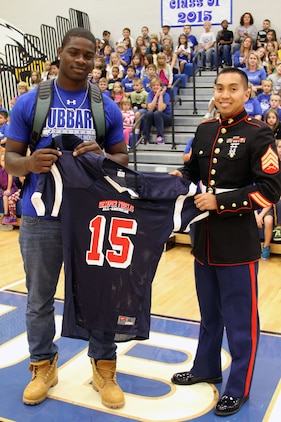 "U.S. Marine Corps Sgt. Albert Opena III, a canvassing recruiter for Recruiting Sub-Station Tri-County, presented a commemorative jersey to Hubbard High School's Larry ""LJ"" Scott for his selection to the Semper Fidelis All-American Bowl game Oct. 3, 2014, in Hubbard, Ohio. The Eagles' star running back will represent the East Team during the bowl game that will which place January 4, 2015 at StubHub Center in Carson, California. (U.S. Marine Corps photo by Sgt. Timothy Stewmam/Released)"