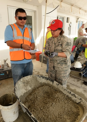 Staff Sgt. Ruth Aguon, Guam Air National Guard 254th RED HORSE Squadron, reviews concrete specifications with an American Concrete Institute instructor during a field concrete testing course in Mangilao, Guam Dec 11. RED HORSE joined with U.S. Naval Base Guam Sailors and Department of Defense civilians to become certified in field testing concrete during a two-day course. (U.S. Air Force photo by Senior Airman Cierra Presentado/Released)