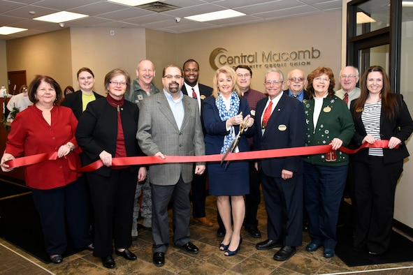 Drema Isaac, with scissors, president and CEO of the Central Macomb Credit Union, uses a large pair of scissors to cut the ribbon on a new location for the credit union at Selfridge Air National Guard Base, Mich., Dec. 18, 2014. The credit union first opened in 1957 as the Selfridge Air Force Base Credit Union. (U.S. Air National Guard photo by Terry Atwell)