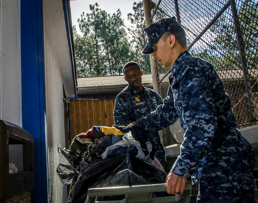 OS1 Strowder and FC1 Byrd, both assigned to the Naval Consolidated Brig Charleston, volunteer their time at Castaways Thrift Shop, Dec. 18, 2014, at Joint Base Charleston - Weapons Station, S.C. The volunteer opportunity was in accordance with CPO 365, a year-round training initiative that Chiefs Messes throughout the Navy take on to prepare first class petty officers to become chiefs. (U.S. Air Force Photo / Senior Airman Tom Brading)