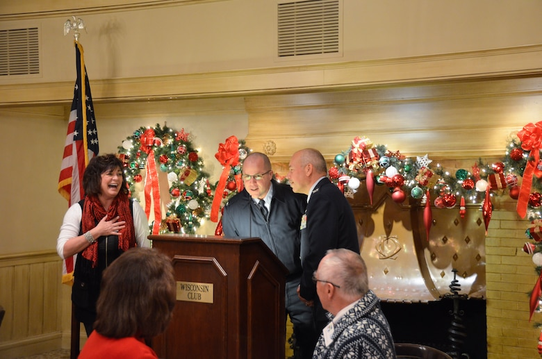 """Janine Sijan Rozina laughs aloud as she watches Col. Daniel S. Yenchesky, wing commander and Col. James V. Locke,  vice commander of the 128th Air Refueling Wing, sing their rendition of """"Five Golden Rings"""" during a 128th Community Council general membership meeting held at the Wisconsin Club, Milwaukee, Dec. 12, 2014. A tradition for the general membership is to close the December meeting with the singing of the  """"Twelve Days of Christmas."""" (U.S. Air National Guard photo by Maj. Sherri A. Hrovatin/Released)"""