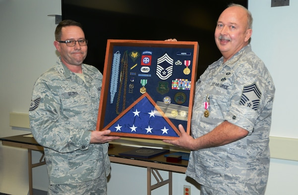 Tech. Sergeant Brian J. Becker and Chief Master Sergeant Charles K. Hoops, 132nd Fighter Wing, Iowa Air National Guard, Civil Engineering Squadron during retirement ceremony on 06 Dec 14 in the CE Building.