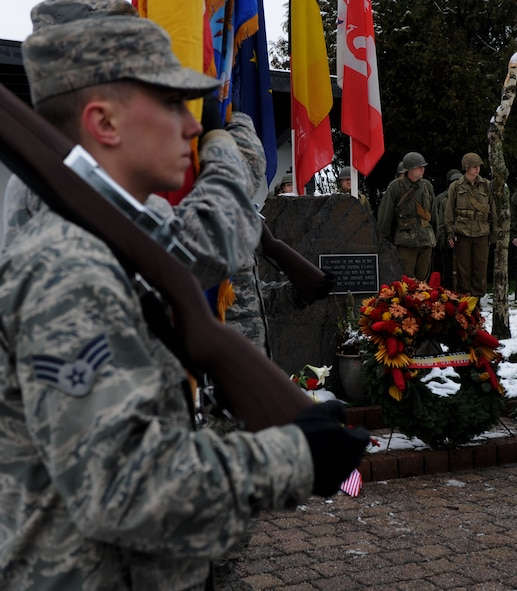 Spangdahlem honor guard members and Battle of the Bulge reenactors stand next to the U.S. Army 106th Infantry Division monument during a memorial ceremony at St. Vith, Belgium, Dec. 14, 2014. The ceremony consisted of a presentation of multiple wreaths, an invocation and speeches from the veterans. (U.S. Air Force photo by Airman 1st Class Luke Kitterman/Released)