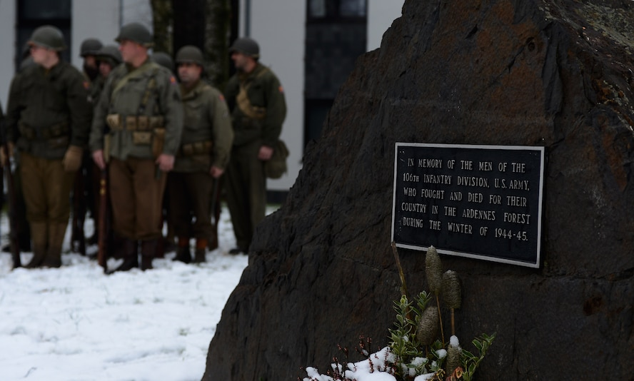 European civilians reenacting the Battle of the Bulge stand in formation next to a memorial monument at St. Vith, Belgium, Dec. 14, 2014. St. Vith dedicated the monument to the U.S. Army 106th Infantry Division men who lost their lives in the battle. (U.S. Air Force photo by Airman 1st Class Luke Kitterman/Released)