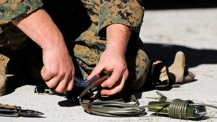 An explosive ordnance disposal technician with Explosive Ordnance Disposal Company, 8th Engineer Support Battalion prepares an explosive during a field exercise Dec. 14, 2014, at EOD site 3 on Camp, Lejeune, N.C. Marines used this method to eliminate a simulated improvised explosive device.