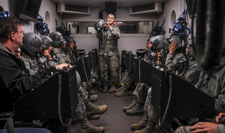 Senior Airman Devin Theis instructs Airmen on the proper use of an oxygen mask during altitude training Dec. 8, 2014, at Little Rock Air Force Base, Ark. Students undergo hypobaric chamber training to experience the effects high altitude has on the body, which include low oxygen levels. Theis is a 19th Aerospace Medicine Squadron high altitude airdrop missions technician. (U.S. Air Force photo/Airman 1st Class Harry Brexel)