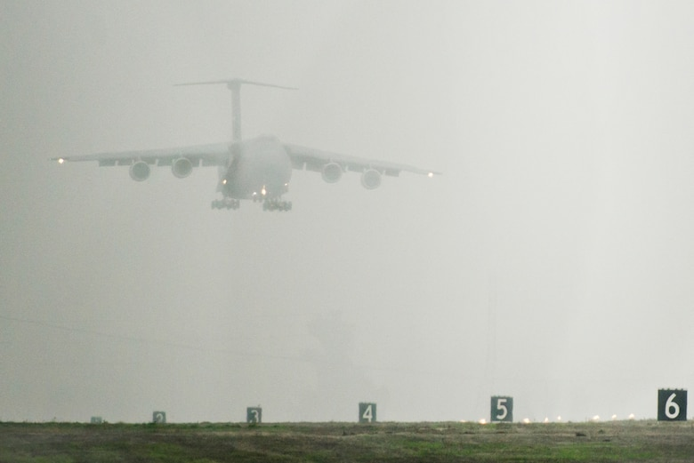 A C-5M Super Galaxy lands on a foggy runway Dec. 10, 2014, at Travis Air Force Base, Calif. The newly modernized aircraft is the fifth C-5M to return to Travis this year following retrograde and refurbishment.  (U.S. Air Force photo/Ken Wright)