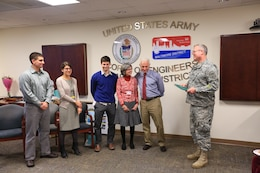 USACE Baltimore chief of operations, receives his retirement certificate from Col. Trey Jordan, USACE Baltimore District commander, after 28 years of federal service alongside his family Dec. 16.